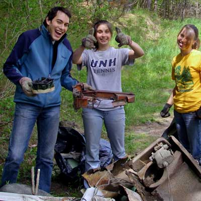 people smile with trash pile