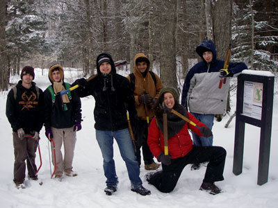 tool wielding people in snowy woods