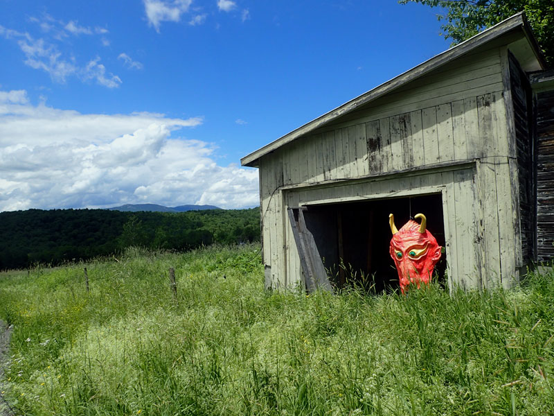 large mask hangs in shed by field