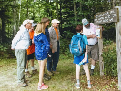 group of hikers look at sign